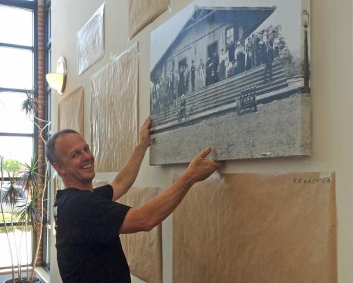 Daniel Baird hangs canvas photographs.