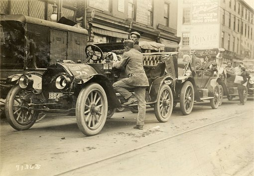 Gernie Mitchell checks his start ticket before boarding the #73 Mitchell for the start in Jersey City. Paul Montague is already in the back seat. Detroit Public Library.