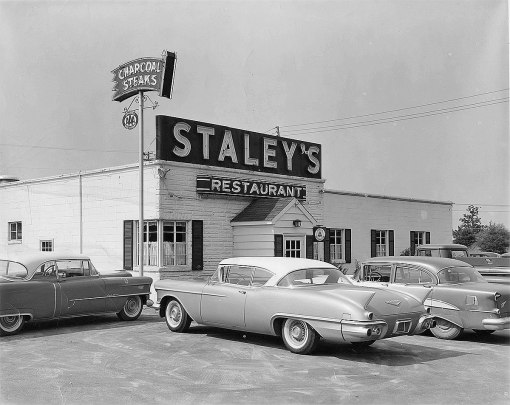 A far cry from the later charcoal steakhouse...note a couple more of Lawrence's collectible Cadillacs...