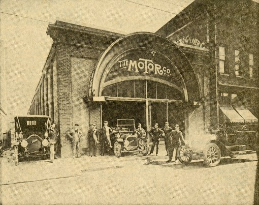 The Motor Company was founded in 1909 by John and Powell Gilmer and Lindsey Fishel, 2nd from left in the picture. The building was located on North Main Street, just across the alley from the Zinzendorf Hotel. Here we see two Buicks in front of the building and a Mitchell parked in the alley. Standing next to the Mitchell is Gernie Miller, who drove the local entry in the 1911 Glidden Tour. Second from the right is Robah Stowe, R.J. Reynolds' personal chauffeur, who drove the local entry in the 1910 Good Roads Tour. Scanned from a North Carolina Room vertical file image.