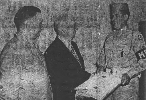 Sgt. Lawrence Staley receives a plaque on behalf of the Fourth Command MPs from David A. Crawford, president of the Pullman Company as Major General Archer J. Lerch looks on. June, 1945.